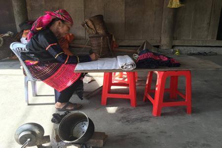 Bà Hồ Thị Lù đang vẽ hoa văn bằng sáp ong.