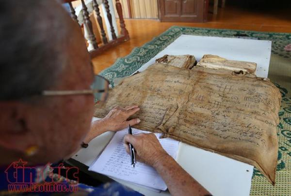 Một độc bản chữ Thái cổ viết trên vải được đặt trên bàn thờ có ý nghĩa trừ tà ma đang được nghệ nhân dịch lại.