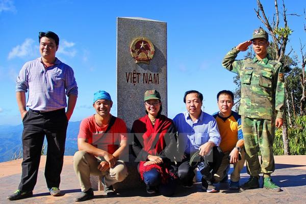 Du khách chụp ảnh kỷ niệm bên cột mốc số 0. Ảnh: Phan Tuấn Anh/TTXVN