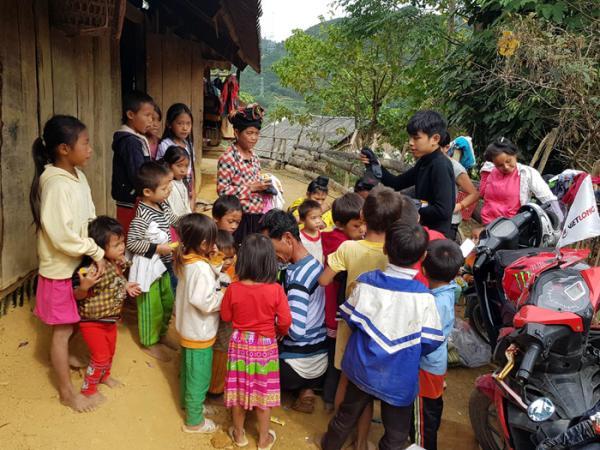 Anh Bùi Khắc Ðoàn trao quần áo từ thiện cho người dân xã Mùn Chung (huyện Tuần Giáo).