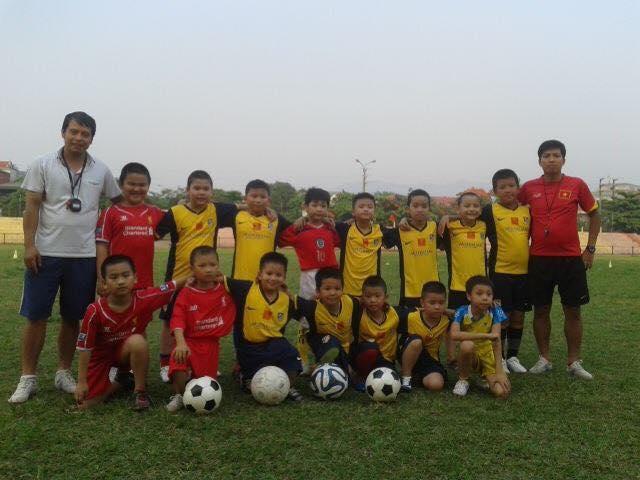 Thầy Nguyễn Công Hoàn ( bên trái ) chụp ảnh lưu niệm cùng các em đội bóng nhí tỉnh Điện Biên