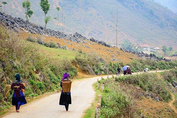 Sáng tinh mơ phụ nữ Mông đã đeo gùi, cầm ô rủ nhau đi chợ phiên.