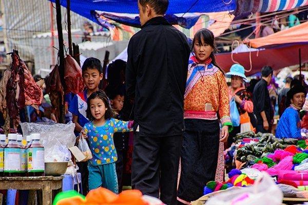 Một bé gái đi chợ phiên cùng chị, thích thú với món quà vặt trên tay.