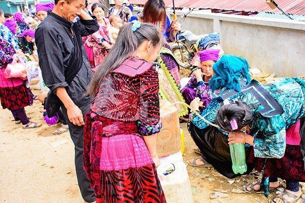 Những phụ nữ Mông bán rượu ngô đang rót rượu từ can ra chai nhỏ cho khách.