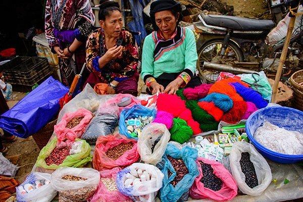Hai phụ nữ bán nông sản và tơ lụa.