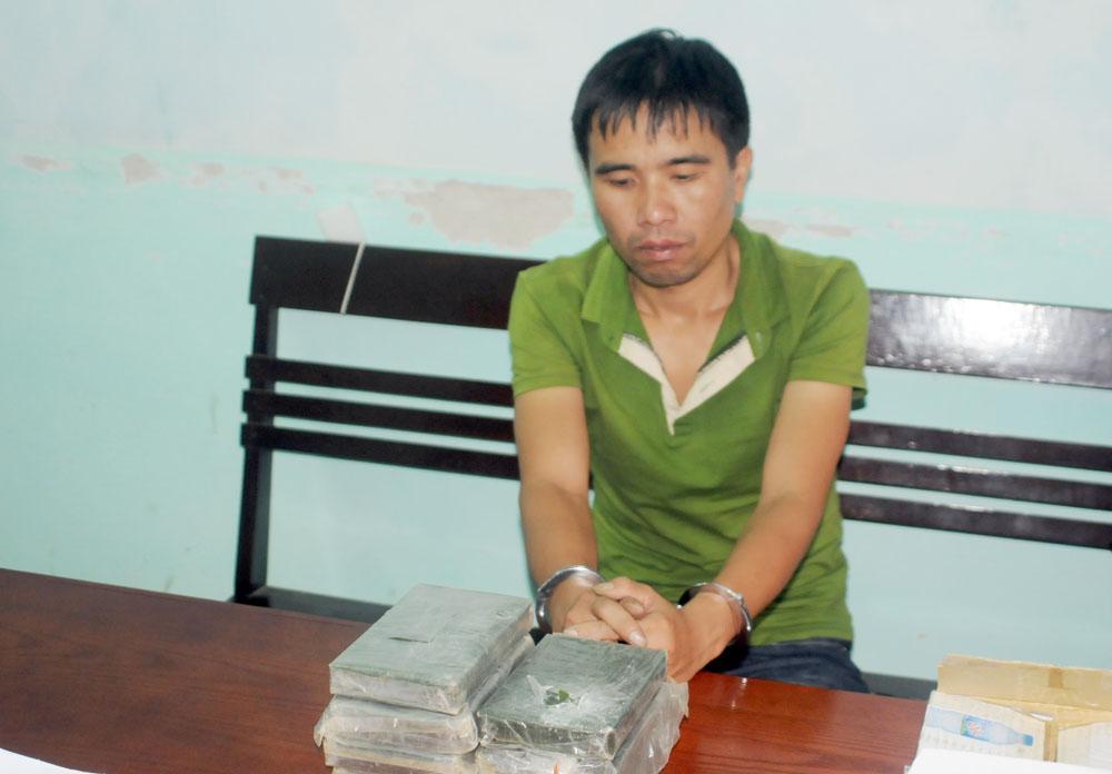 Lò Văn Si với tang vật là 7 bánh hêrôin bị bắt giữ tại cơ quan công an. Ảnh: baophutho.vn