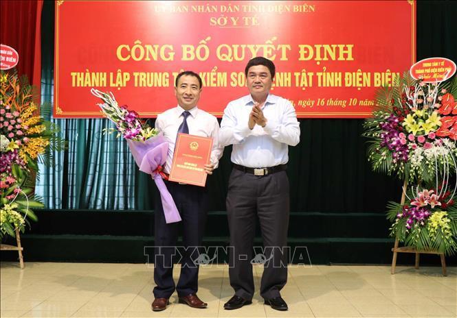 Phó Chủ tịch UBND tỉnh Điện Biên Lê Văn Quý (phải) trao Quyết định cho đại diện Phụ trách Trung tâm kiểm soát bệnh tật tỉnh Điện Biên Đoàn Ngọc Hùng.