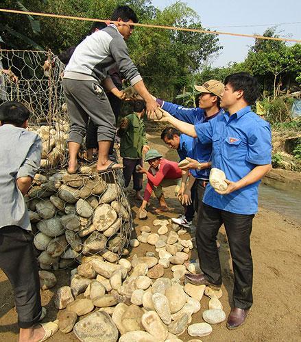 Ðoàn viên, thanh niên huyện Ðiện Biên Ðông giúp người dân bản Mường Luân 2, xã Mường Luân làm cầu tạm. Ảnh: Mai Giáp