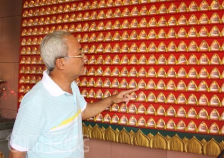Ông Chung Anh Tùng đang giới thiệu việc gửi giấy cầu an tại chùa