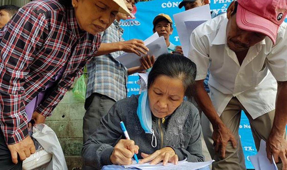 Một nữ công nhân xấp xỉ 50 tuổi đang viết đơn xin việc ở công ty mới