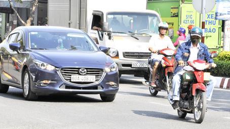"""Nhiều người chạy xe máy vô tư """"cúp đầu"""" xe ô tô gây nguy cơ tai nạn giao thông."""