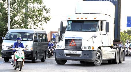 Một người điều khiển xe máy chạy vượt lên trước đầu xe ô tô, xe container tại khu vực cầu Sập (TP.Biên Hòa).