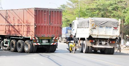 Trong lúc 2 xe tải lớn đang vượt nhau, nam thanh niên vừa điều khiển xe máy vừa nghe điện thoại len lỏi giữa 2 xe, rất nguy hiểm. Ảnh chụp trên tỉnh lộ 767, đoạn qua huyện Trảng Bom.