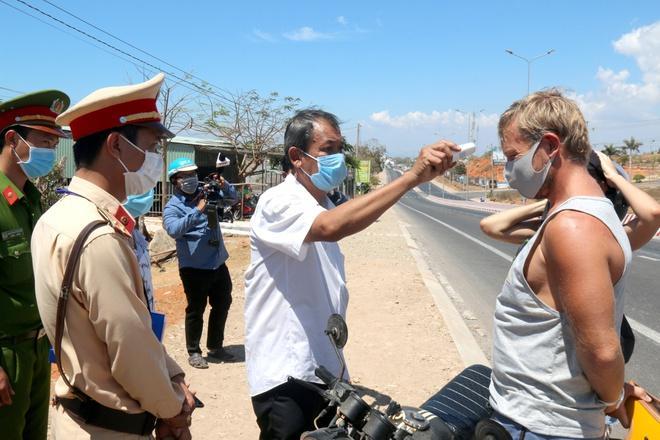 Đo thân nhiệt tại chốt kiểm tra du khách nước ngoài trên đường Nguyễn Thông (Phú Hài, TP. Phan Thiết). Ảnh: Tuấn Kiệt.