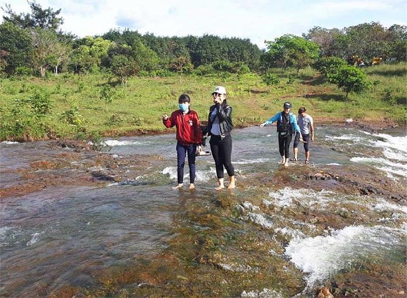 Hình ảnh của một nhóm học sinh đang tạo dáng chụp hình để lưu lại kỷ niệm khi cùng nhau khám phá vẻ đẹp của thác nước.