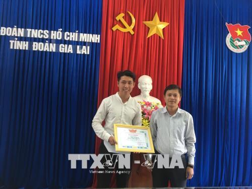 Anh Trần Vũ Luân (trái) nhận Bằng khen từ lãnh đạo tỉnh đoàn Gia Lai. Ảnh: Hồng Điệp/TTXVN