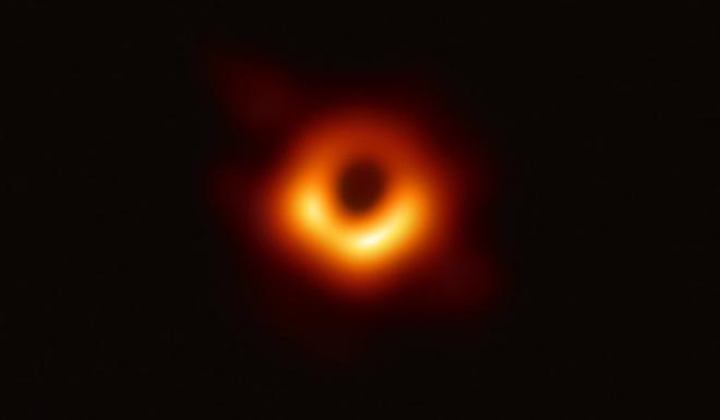Ảnh chụp đầu tiên về hố đen siêu khối lượng ở trung tâm của thiên hà M87 được công bố ngày 10/04/2019. Có thể thấy một vành sáng da cam tạo ra bởi sự uốn cong của các tia sáng dưới trường hấp dẫn mạnh xung quanh hố đen có khối lượng gấp 6,5 tỷ lần khối lượng Mặt Trời. Nguồn: EHT