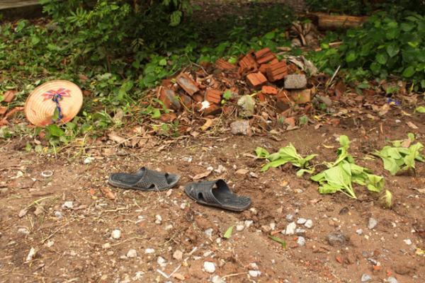 Tại hiện trường chỉ còn chiếc nón và đôi dép của nạn nhân cạnh luống rau đang trồng. (Nguồn: Đức Tùy)