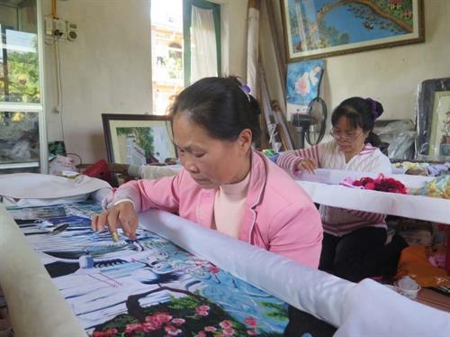 Nghệ nhân ưu tú Nguyễn Thị Hoan (người phía trước) miệt mài bên khung thêu. Ảnh: Mạnh Minh- TTXVN