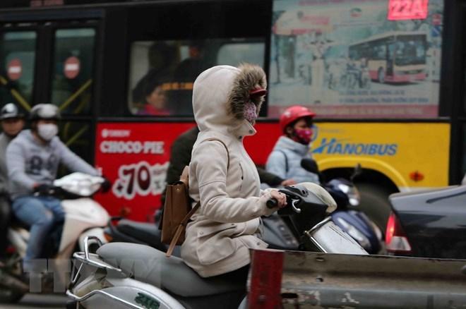 Người dân tham gia giao thông trong trang phục kín mít để tránh rét. (Ảnh: Thành Đạt/TTXVN)
