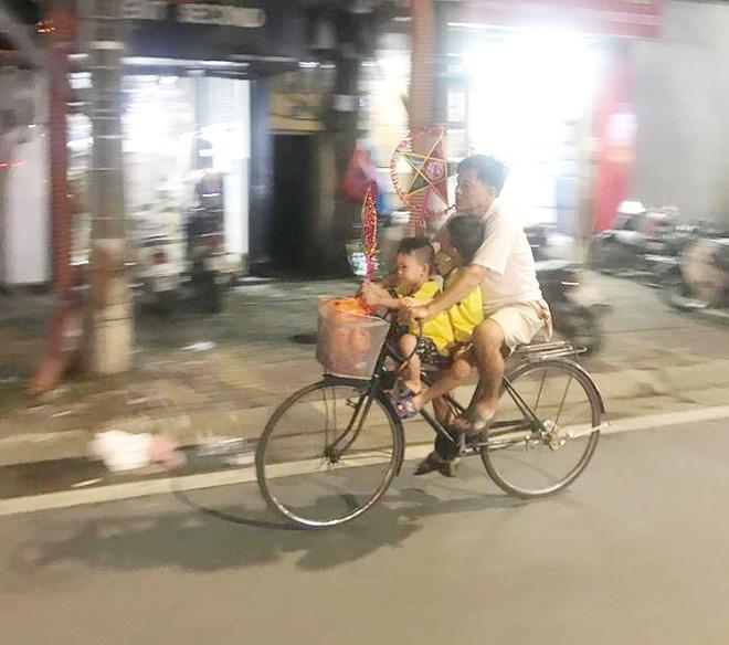 Giữa đoạn đường ồn ào và tấp nập, cha cứ lặng lẽ đèo 2 con đi chơi trên chiếc xe đạp giản dị như thế. Ảnh: Hương Ngân