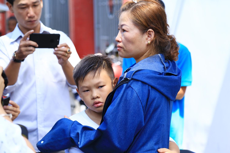 Chị Dung ôm con trai và động viên trong lúc chờ nhận thi thể chồng cũ. (Ảnh: Xuyến Chi)