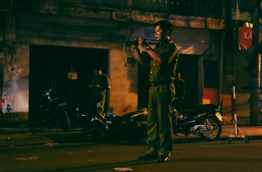 Một điều tra viên chụp lại hiện trường để phục vụ điều tra, truy xét các đối tượng cướp giật.