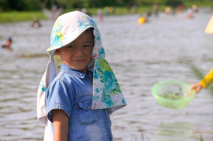 Nhiều em nhỏ được bố mẹ che khăn trùm đầu để chống nắng gắt.