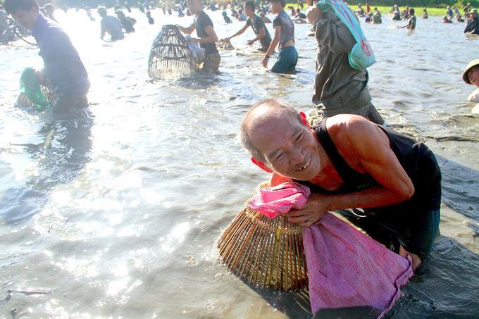 Khi cá mắc trong nơm, người dân sẽ dùng tay bắt bỏ vào bao tải mang bên hông.