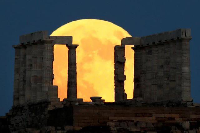 Nguyệt thực kéo dài từ 00h14 đến 6h28 ngày 28/7, trong đó nguyệt thực toàn phần bắt đầu từ 2h30 đến 4h13 (kéo dài khoảng 1 giờ, 42 phút, 57 giây). Ảnh: Nguyệt thực toàn phần được nhìn thấy từ ngôi đàn Poseidon, gần thủ đô Athens, Hy Lạp.
