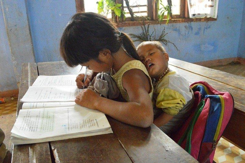Cô bé vừa giữ em ngủ vừa học bài. Ảnh: Dân sinh