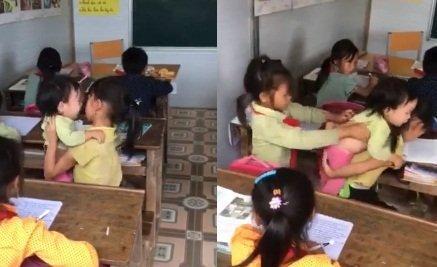 Bé gái vùng cao vừa viết chữ vừa chăm em khóc giữa lớp học.
