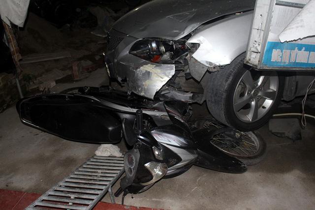 Phần đầu xe ô tô bị hư hỏng và bánh phải phía trước đè lên xe máy