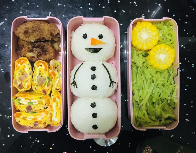 Trứng cuộn, ức gà rán, cơm nặn hình người tuyết, ngô luộc và bí xào