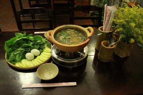 Nồi lẩu cháo cua đồng thơm ngon được dùng kèm với nhiều loại rau. Ảnh: monanmientay.