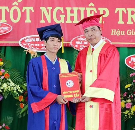 Ông Trần Văn Trung (phải), Hiệu trưởng Trường Trung cấp Kỹ thuật – Công nghệ tỉnh, trao bằng tốt nghiệp cho các học viên.