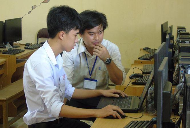 Em Phú được thầy Hưng hướng dẫn lập trình phần mềm. Ảnh: Kim Hà.