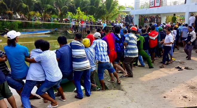 Hơn trăm người kéo hai nắp cống để cứu nạn nhân. Ảnh: Nhật Tân.
