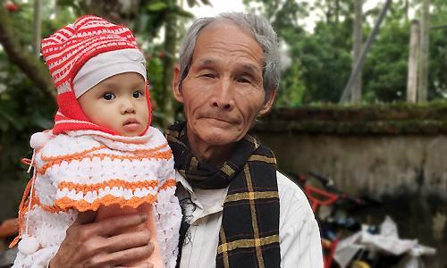 Ông Học và con gái út được 15 tháng tuổi. Ảnh Phan Dương.