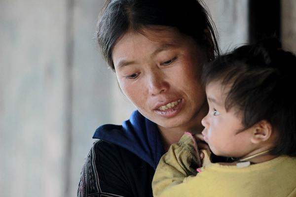 Chị Mùa Thị Sua ôm con gái út cố kìm nén nỗi đau đớn tột cùng