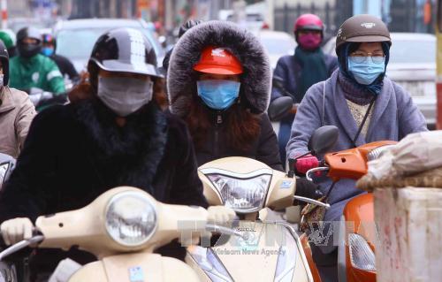 Người dân Hà Nội ra đường với trang phục kín mít để tránh rét. Ảnh: Quang Quyết/TTXVN
