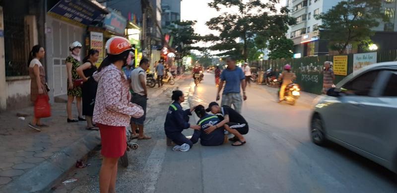 Người đi đường đỡ chị Tâm lên chờ ô tô đưa đi cấp cứu