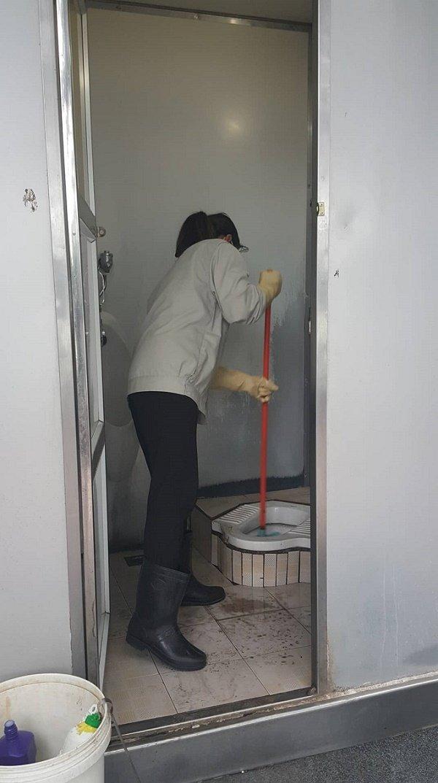 Nữ công nhân dọn dẹp nhà vệ sinh