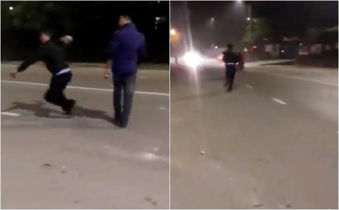 Người chồng cầm gạch ném, chạy theo xe máy của vợ trong vô vọng - Ảnh cắt từ clip.