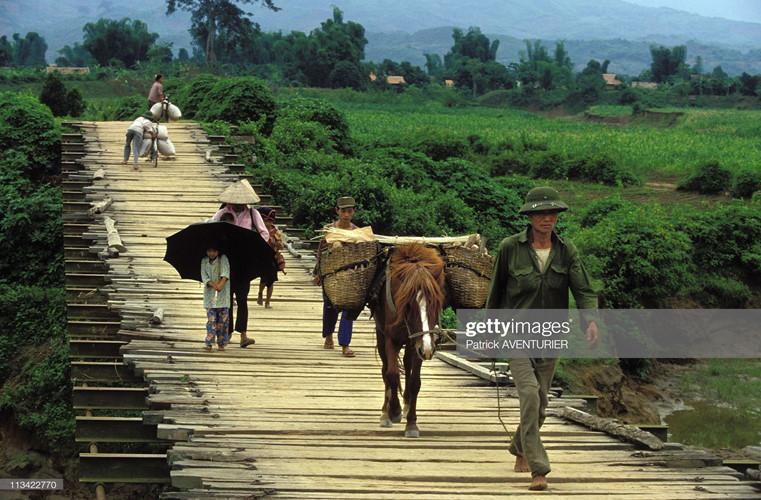 Người dân di chuyển trên cây cầu bắc qua sông Nậm Rốm.