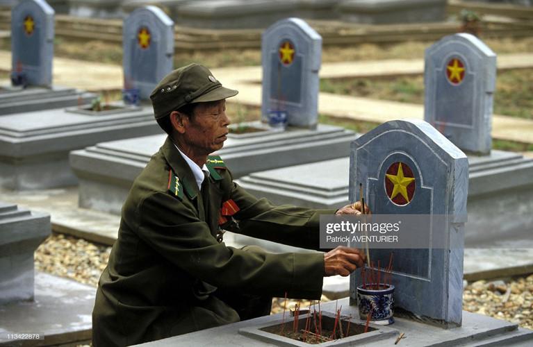 Người cựu binh già thắp hương cho đồng đội tại một nghĩa trang liệt sĩ ở Điện Biên Phủ.