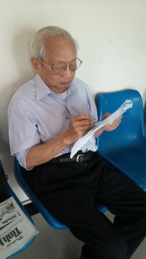 Cụ Trương Gia Nhẫn ngồi tại nhà sinh hoạt cộng đồng còn tranh thủ học.