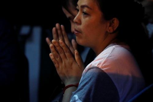 Người nhà các bé trai cầu nguyện gần hang Tham Luang. Ảnh: Reuters.