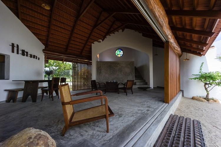 Phòng khách thoáng đãng, mộc mạc với bộ bàn ghế gỗ truyền thống.