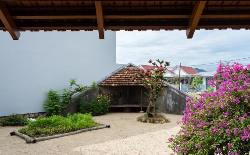 Khoảng sân trước nhà nổi bật với cây xanh và hoa cỏ.